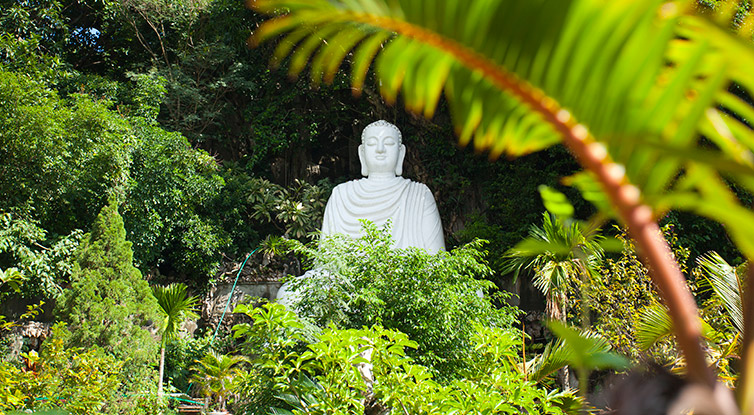 A statue of a buddha sits in a lush garden at the Marble Mountains in Danang
